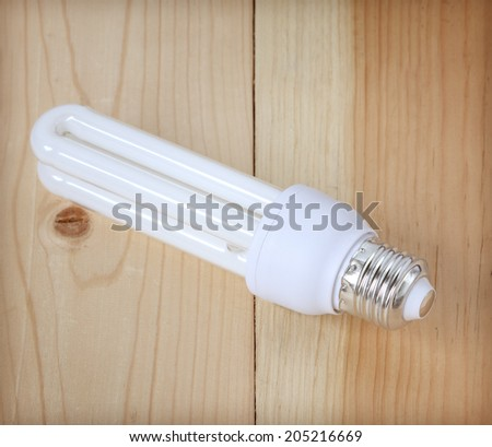 white energy saving bulb on wooden floor - stock photo