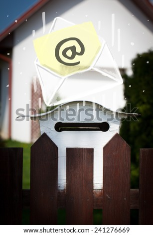 White envelope with email sign dropping into mailbox - stock photo