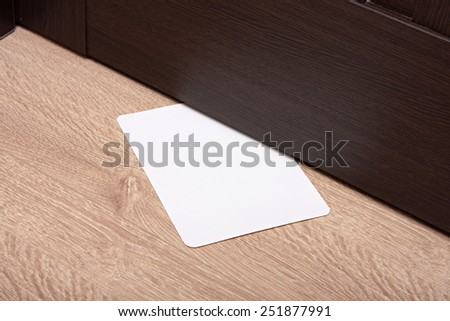 white envelope with message slipped under wooden door. - stock photo