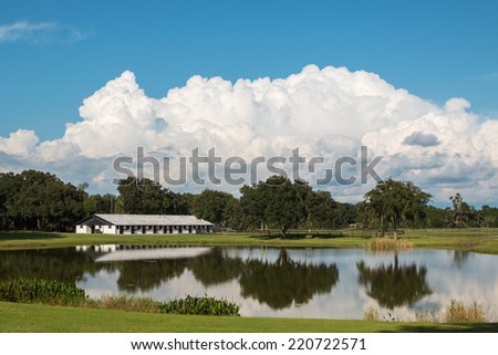 White equine horse barn on farm ranch with reflection in water pond lake - stock photo