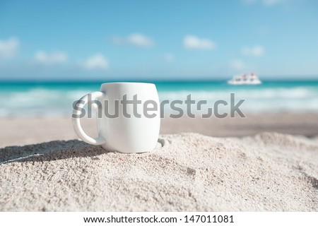 white espresso coffee cup with ocean , beach and seascape. Shallow dof. - stock photo