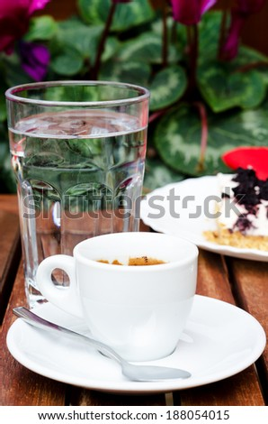 White espresso cup and a piece of blackberry cheesecake standing at the street cafe table - stock photo