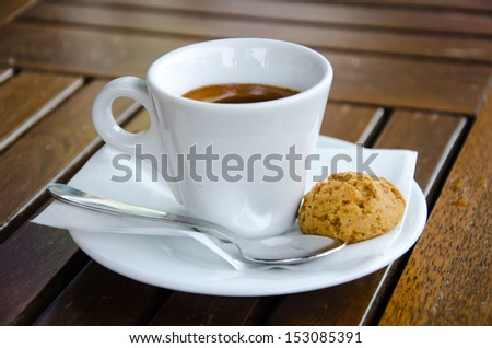 White espresso cup with biscuit standing on the wooden table - stock photo