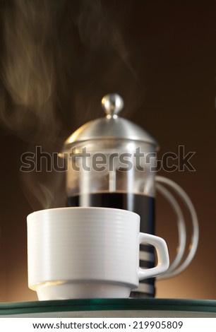 White Espresso cup with  steaming coffee and a French Press/Cafetiere  - stock photo