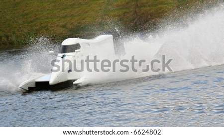 White F1 speed boat racing through the water - stock photo
