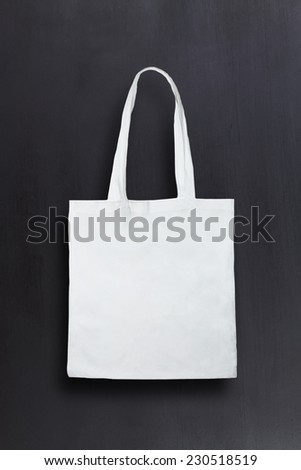 White fabric bag against chalkboard background - stock photo