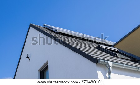 white facade with solar panels and gutters