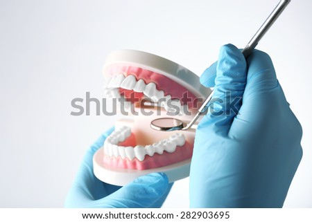 White fake teeth in hand of dentist, isolated on white - stock photo