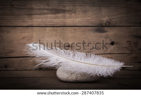White feather and a stone on wooden dark background for mourning concepts. - stock photo
