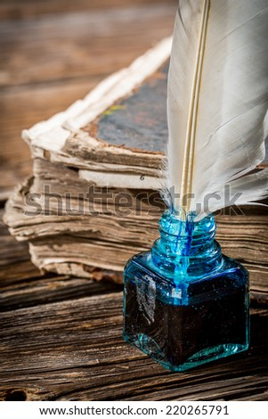 White feather on blue inkwell and old book - stock photo