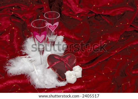 White feathers, wine glasses and a red heart on a valentine backdrop with room for text. - stock photo