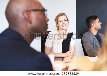 White female executive smiling at camera during a work meeting.