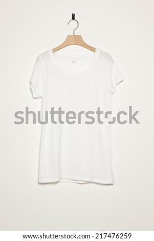 white female t-shirts with wood hanger isolated white. - stock photo