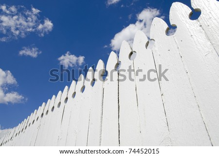 White fence and blue sky with clouds - stock photo