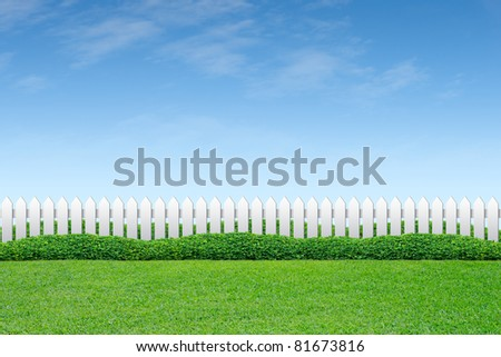 White fence and green grass on blue sky - stock photo