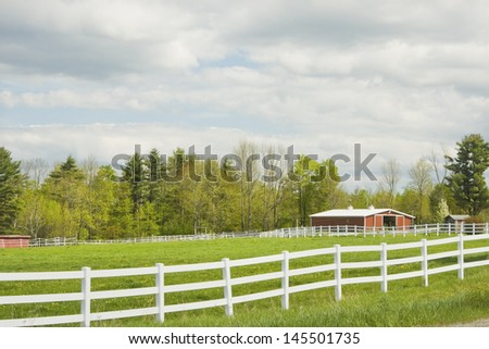 White fence and pasture outside red barn on farm in Maine. - stock photo