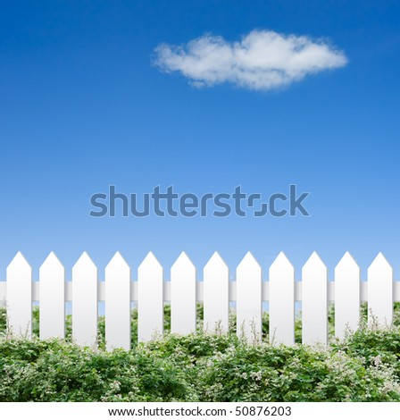 White fence and shrubs shot against cloudy sky