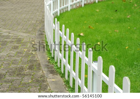 White fence around front yard of residential house - stock photo