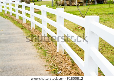 white fence at the roadside - stock photo