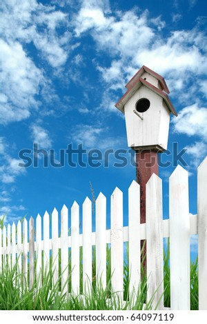 white fence with bird house - stock photo