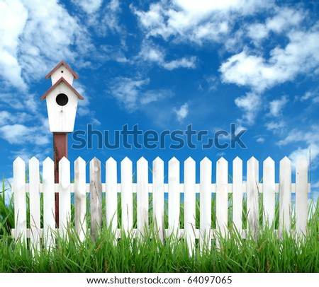 white fence with bird house and blue sky - stock photo