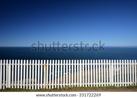white fence with ocean background - stock photo