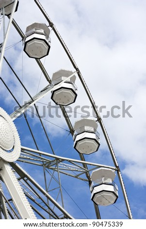 White ferris wheel and cloudy sky