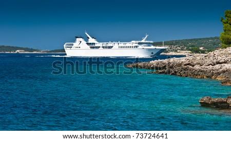 White ferry boat  near small Adriatic island coastline. Clear azure sea water under blue sky. Korcula island, popular touristic destination of Croatia. - stock photo