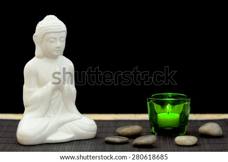 White figure in meditation pose with pebbles and candle in a green glass from point of view - stock photo