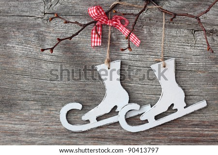 White   figure skates decoration over wooden background