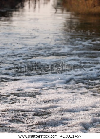 white fine bubbles flowing on water surface running from a pipeline direct onto a agricultural farm water canal - stock photo
