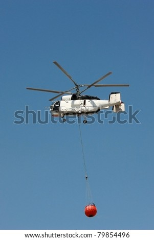 White Fire rescue helicopter with water bucket - All copyrighted elements removed - stock photo