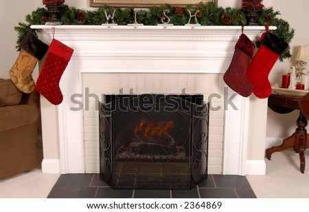White fireplace decorated with stockings and pine for Christmas - stock photo