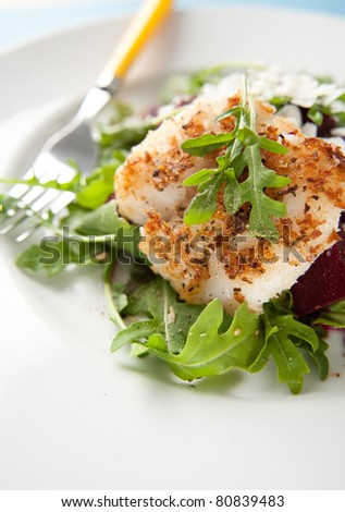 White Fish Fried in Coconut Flakes and Served with Fresh Arugula and Beets - stock photo