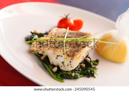 white fish with spinach - stock photo