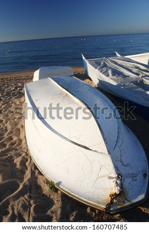 White fishing overturned boat on sand with near sea in the morning - stock photo
