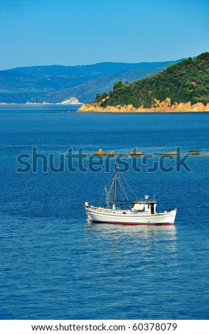 White fishing trawler anchored among islands of the Aegean Sea - stock photo