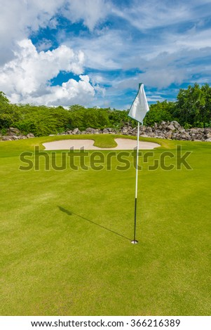 White flag and sand bunkers at the beautiful golf course. Vertical. - stock photo