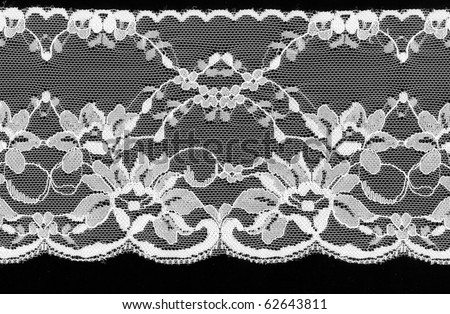 White floral lace on a black background. - stock photo