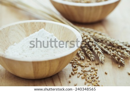 White flour and wheat on wooden table - stock photo