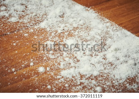 White flour on wooden table with line