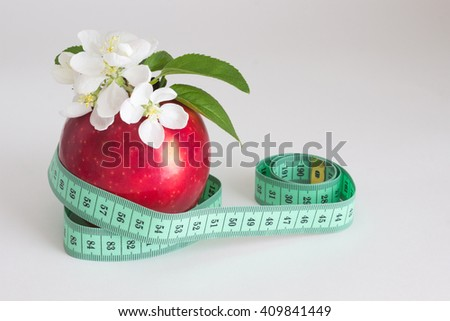 White flower on a red apple and centimeter on a white background - stock photo
