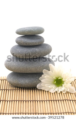 White flower with stack of pebbles on mat - stock photo