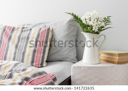 White flowers and books on a side table near a bed. Fresh design. - stock photo