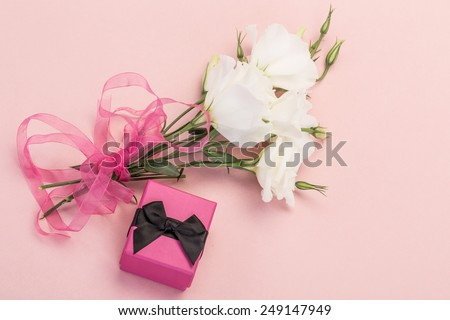 white flowers and gift on pink - stock photo