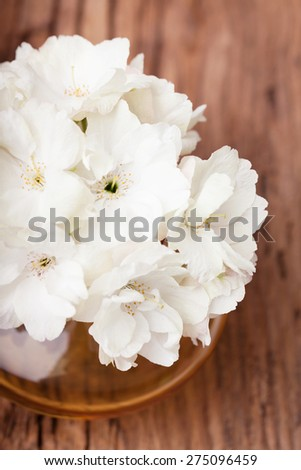 White flowers  in a glass vase  on a vintage surface