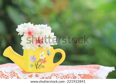 white flowers in a small vase in the garden - stock photo