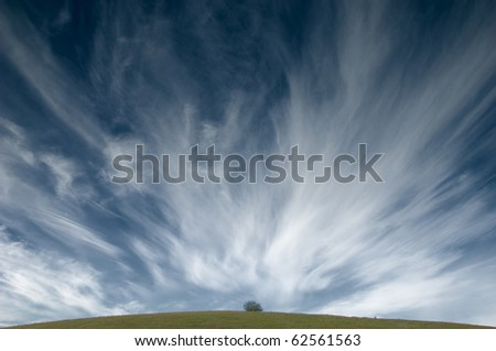 White fluffy clouds in the blue sky appearing from the hill - stock photo