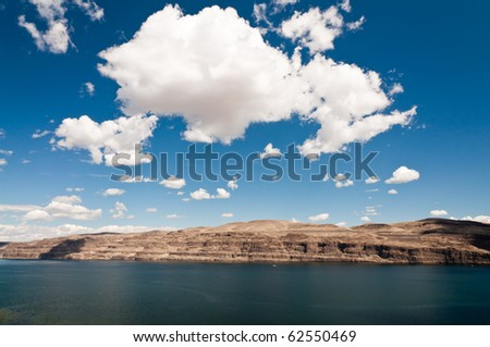 White fluffy clouds on bright blue sky  over the Columbia River in Eastern Washington - stock photo