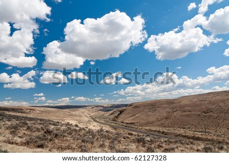 White fluffy clouds on bright blue sky  over the hill in Western Washington - stock photo
